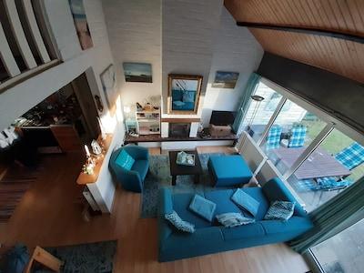 Wohnzimmer mit Kamin und anschließender Terasse und Garten