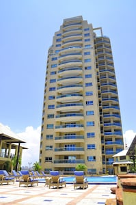 Apartment tower watches over common area pool and Caribbean Sea.