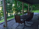 Guest patio with grill, table, chairs, chaise loungers