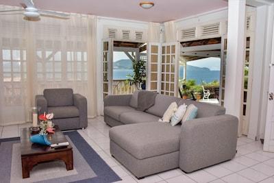 Salon  portes ouvertes sur la terrasse avec vue sur la baie