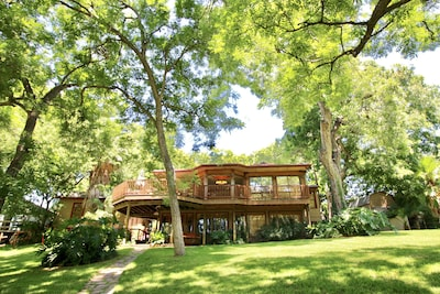 View of the home from the lake side. Gotta love those 100 year old pecan trees!