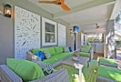 Ground level porch features sitting area, bar with TV and table.