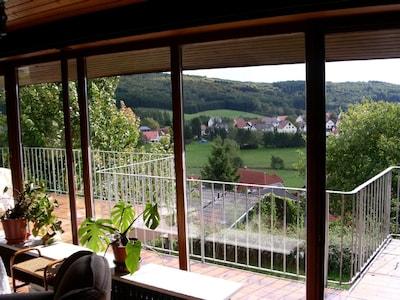 Panoramablick mit Dorf und Hügelkette