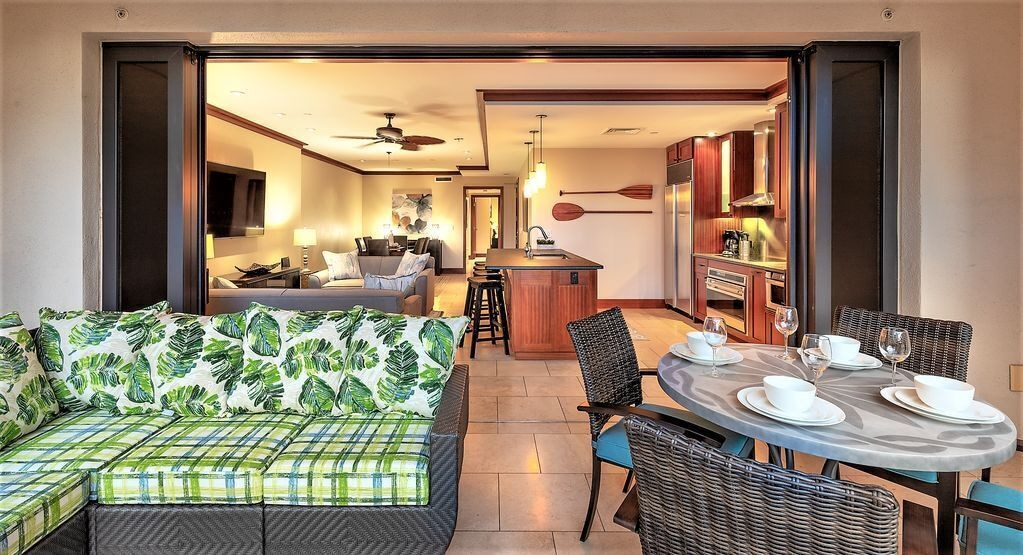 Image of the interior of a Hawaii villa with a dining area and two living areas.