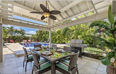 Enjoy the lush garden and tiled pool from the covered gazebo.