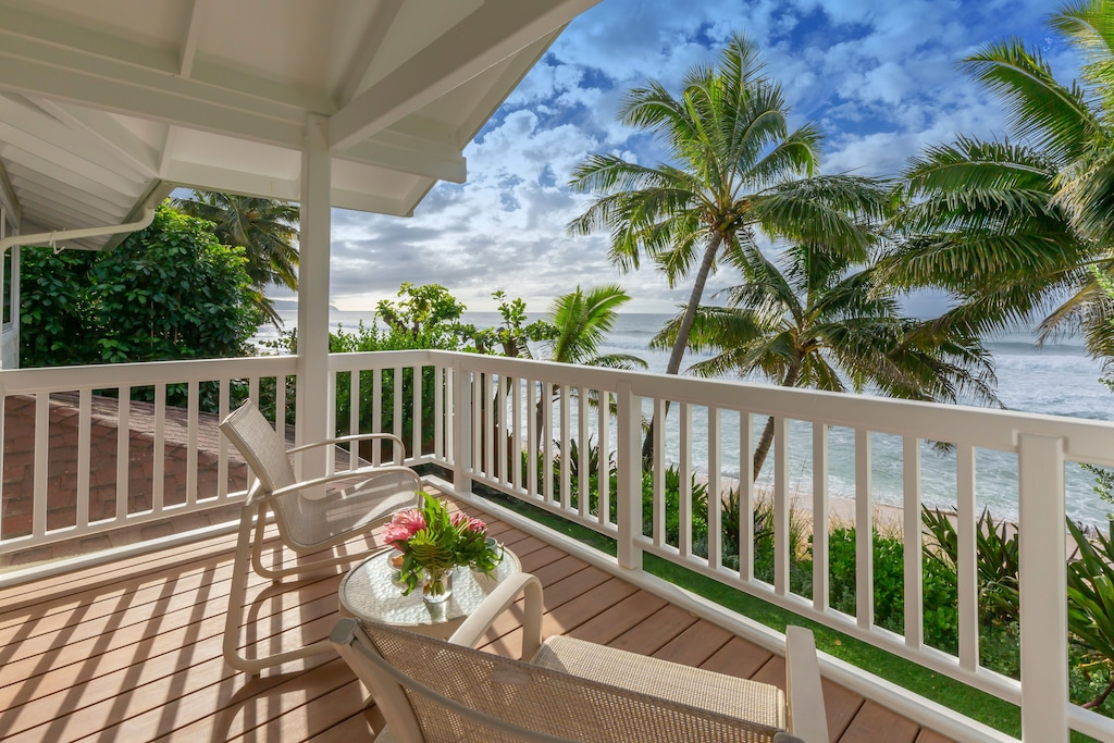 Find out the best villas on Oahu recommended by top Hawaii blog Hawaii Travel with Kids Image of a lanai overlooking the ocean and palm trees.