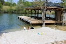 Beach w/ sandy bottom for easy access into water. Deep water is off end of dock.