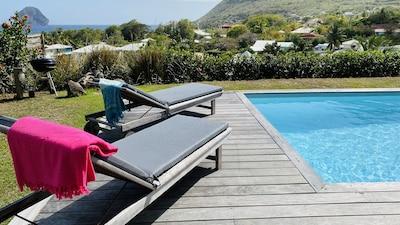 Transats bain de soleil au bord de la piscine et hamac sur la véranda