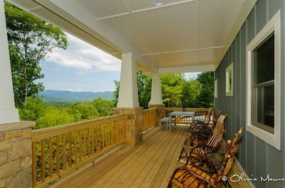 Rocking chairs on a huge covered proch with view and dining.