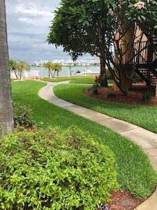 Sidewalk leads to the front door, just steps from the water.