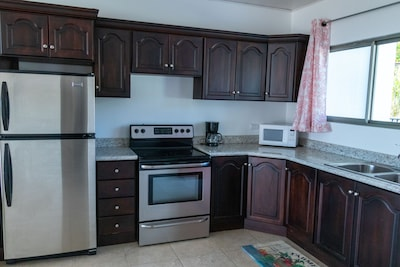 Kitchen with full refrigerator, etc.