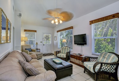 Spacious living area with three comfy chairs and sleeper sofa.