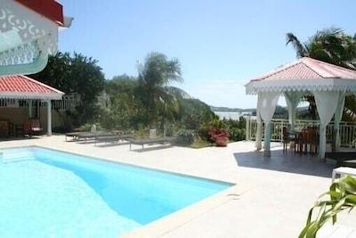 vu du salon sur la piscine la terrasse et la vue panoramique donnant sur la mer
