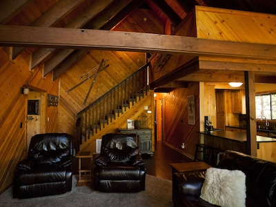 Cozy living area with leather recliners and sofa, large flat screen TV and a window wall looking out at the towering pines