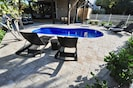 Heated swimming pool with lounge chairs, dining table and Weber gas BBQ