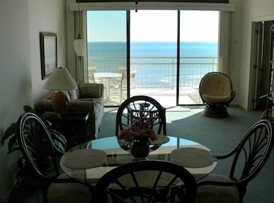 Looking from kitchen through living room to front balcony & ocean in backround