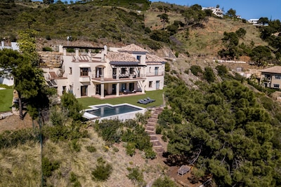 Villa photographed by a drone showing decking area below pool