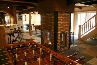 game room with air hockey, wood burning fireplace, wet bar with fridge and sink