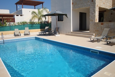 Lovely pool area with 6 sun beds and parasols and a shaded eating area.