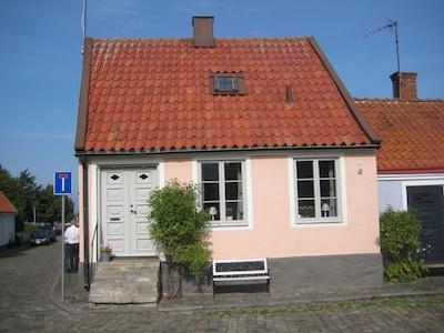 Rosa gatuhuset från lilla torget med pumpen. Gatan vänst leder mot småbåtshamnen