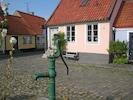 Rosa huset med pumpen på lilla torget i Gamla Stan mitt bland gatuhusen