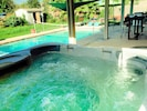 8 person Sundance hot tub on the back patio.  Pool has a volleyball net.