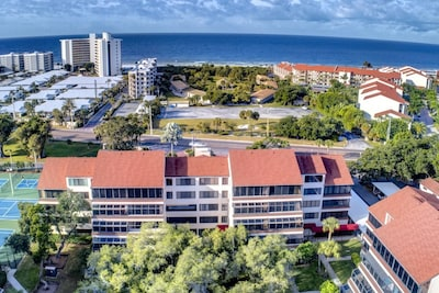 The condo is located in this building facing the park-like grounds with a short stroll to the Bayside water views.  Tennis/Pickleball around the corne