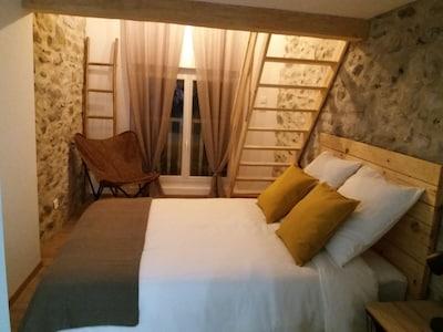 Chambre avec lit en 140cm, fauteuil et penderie.