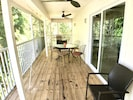 Screened-in porch with fans, gas grill, cloth stand, and table and chairs.