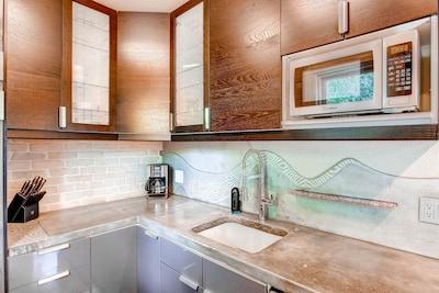 Gourmet Kitchen: Gas stove, custom concrete counter, exposed brick