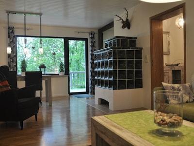 Wohnzimmer mit Kachelofen und Ausgang zur Balkonterrasse