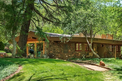 A quaint stone clad cabin with rustic charm set in the trees on Oak Creek in Sedona