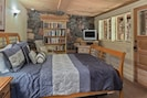 The bedroom has a queen size bed, TV and library of books