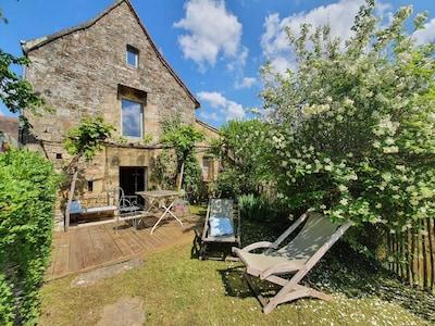 Façade avec terrasse en bois à l'ombre de la vigne, coin jardin et ses transats.