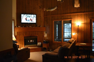 Cozy living room with fireplace and large screen TV.