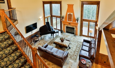 Large great room with fireplace, grand piano and open to dining and kitchen area