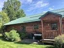 Back of Moose Horn Lodge, propane BBQ grill, manicured lawn, mature trees