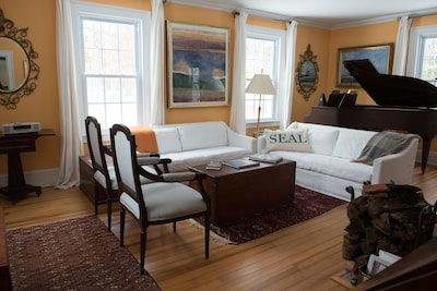 Living room with baby grand piano and fireplace