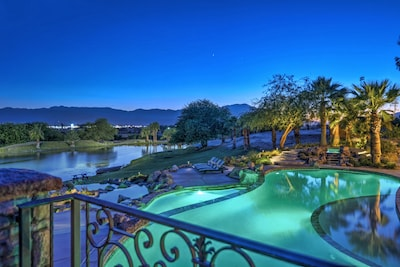 View of private lake with mountain views from bridge over pool.