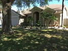 Paradise Retreat Front of home with tropical plantings, 2 car garage fenced yard