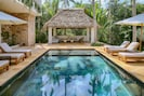 Looking across a serene pool to our new 500 sq. ft. outdoor palapa living room.