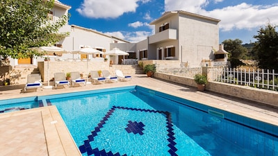 Overview of the villa and pool area with sun beds, umbrellas and sitting areas