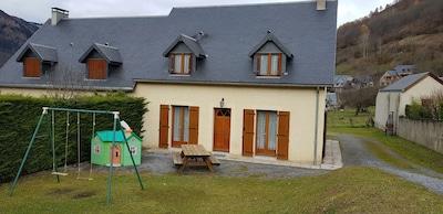 maison clôturée avec salon de jardin, balançoire et maison d'enfants