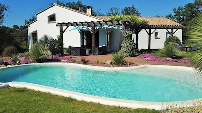 Vue générale de la villa côté piscine et jardin.