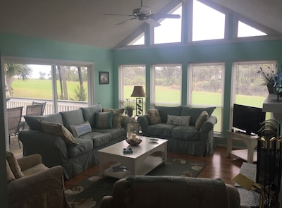 Living room with glimpse of golf course and deck.