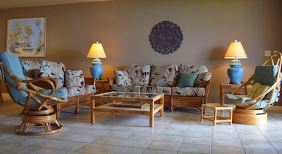 Spacious living area with new furnishings, TV, and ocean view.