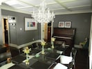 Dining room chandelier, antique piano, tile ceiling.