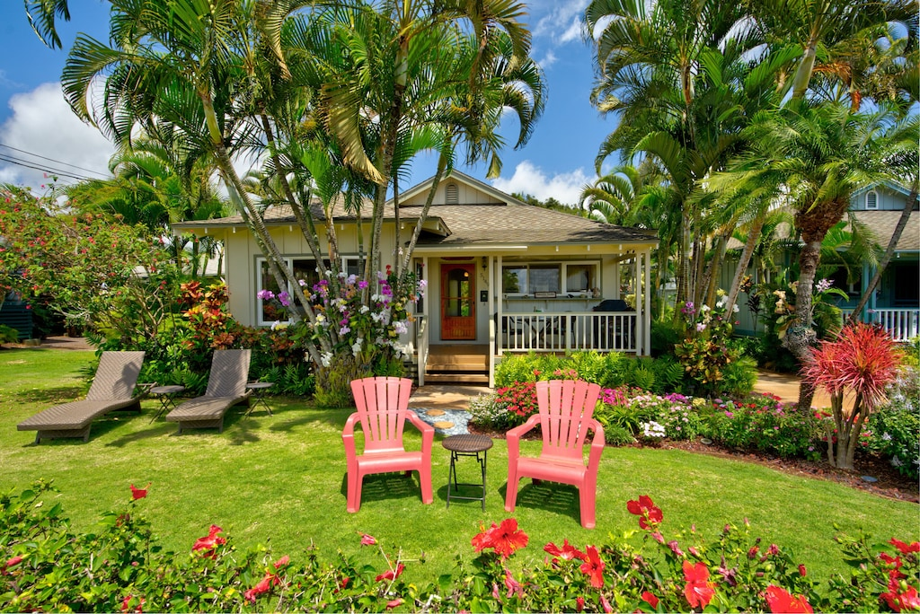 Cute cottage with red accents amidst a tropical garden