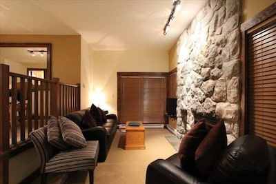 Seating area with stone fireplace and flat screen TV