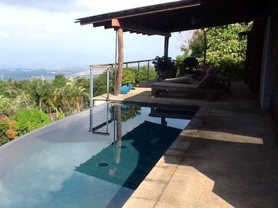 West-facing 180 view lanai with lap pool, teak dining set, BBQ